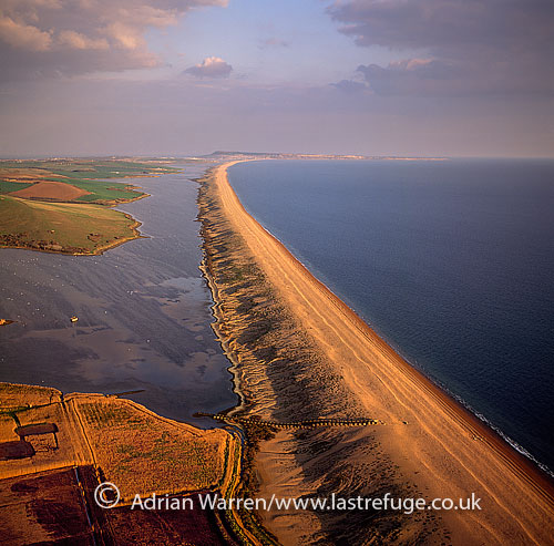 Chesil Beach (Chesil Bank), 29 km long shingle beach, Dorset. A tombolo connecting mainland to the Isle of Portland. It is a part of the Jurassic Coast, England