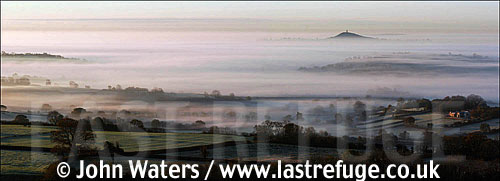 Panorama: View from Mendip Scarp overlooking misty Somerset countryside, Glastonbury Tor in distant, Somerset, UK