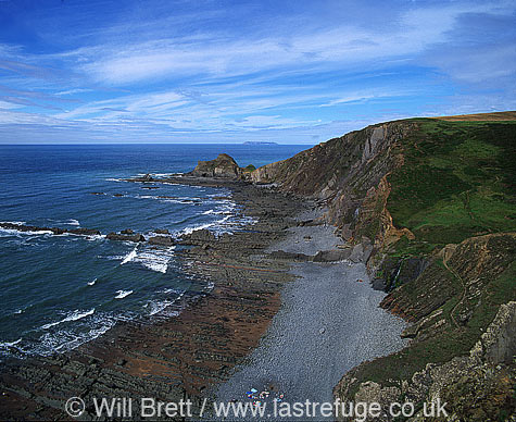 Blegberry Beach north of Hartland quay looking north. Showing south west coast path running along cliff, pebble beach at low tide, Gull Rock and Lundy Island on horizon