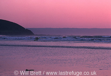 Twilight at Westward Ho! Beach looking southwest towards Greencliff. Surfers enjoying a late session
