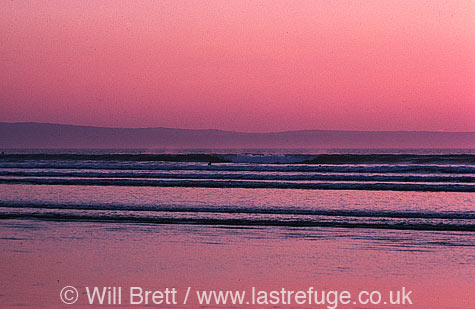Twilight at Westward Ho! Beach looking southwest towards Clovelly over bideford bay. Surfers enjoying a late session