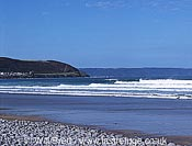 Summer surf at Westward Ho! Beach looking southwest showing pebble ridge in foreground and greencliff with bideford bay in background