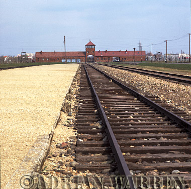 Auschwitz Nazi Death Camp: The railway siding where the selections of arriving prisoners took place, with the main entrance archway, watch tower and SS guardhouse in the background.