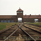 Auschwitz Nazi Death Camp: The railway siding inside Birkenau camp, with the main entrance archway, watch tower and SS guardhouse in the background.