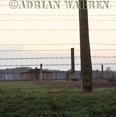 Auschwitz Nazi Death Camp: The electrified perimeter fence at Auschwitz II - Birkenau with remains of wooden accommodation blocks beyond.