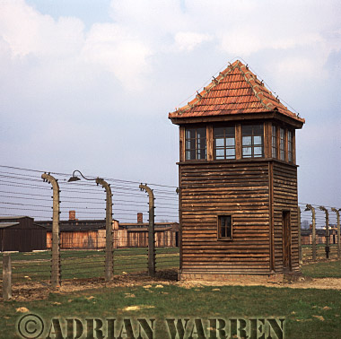 Auschwitz Nazi Death Camp: Guard watch tower and the electrified perimeter fence at Auschwitz II - Birkenau, with wooden accommodation blocks beyond