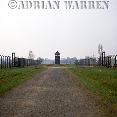 Auschwitz Nazi Death Camp: Auschwitz II - Birkenau : Guard watch tower overlooking road leading from the railway sidings to accommodation areas which were separated from one another by barbed wire fences.