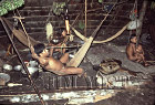 Waorani Indians: The nuclear family clusters around their fire in the longhouse, Gabado, 1973, Ecuador