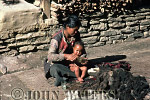 Tibetan woman anointing baby with oil, Tatopani, Nepal, Asia
